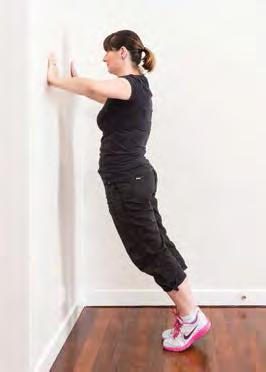 From a standing position, place both hands on the wall, shoulder-width
