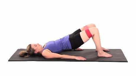 Bridge with Hip Abduction and Resistance - Ground Touches Begin lying on your back with your feet resting on the ground, arms by your sides, and a resistance band looped around your legs above your