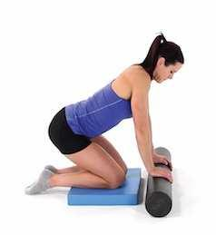 Lean back and slightly toward one side, using your arms for stabilization, then roll yourself back and forth over the foam roller.
