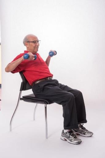 SEATED CHEST PRESS - DUMBBELLS Sit on a chair with your feet hip-distance apart. Bring dumbbells to the side of your chest. Straighten your arms.