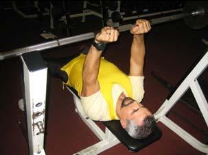 Primarily using the muscles at the back of the upper arms (triceps), lower the body until the elbows are at 90 degrees.
