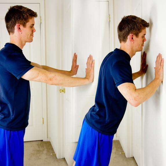 WALL PUSH UPS Standing at a wall; place your arms out in front of you with your