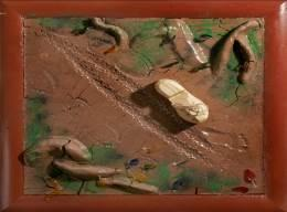 board with clay in his bare feet to make a foot print.