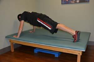 Keep your back straight and do not let your stomach sag. Action: Slowly bend your elbows, lowering your trunk and thighs toward the surface of the mat.