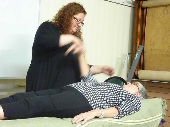 Richelle checks guest Karen s muscles Kinesiology uses muscle monitoring to gather information about a person s well-being.